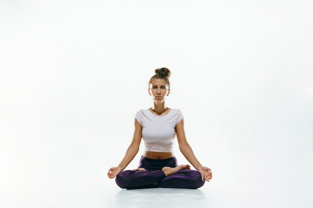 Sporty young woman doing yoga practice isolated. fit flexible female model practicing. concept of healthy lifestyle and natural balance between body and mental development.