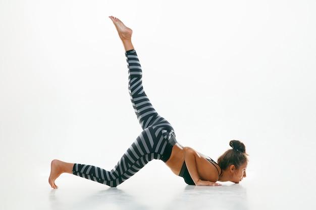 Giovane donna sportiva che fa pratica di yoga isolata. misura la pratica del modello femminile flessibile. concetto di stile di vita sano e equilibrio naturale tra corpo e sviluppo mentale.