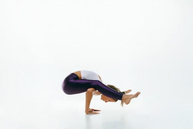 孤立したヨガの練習をしているスポーティな若い女性。練習中の柔軟な女性モデルにフィットします。健康的なライフスタイルと身体と精神の発達の間の自然なバランスの概念。