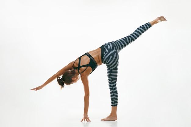 고립 된 요가 연습을 하 고 스포티 한 젊은 여자. 유연한 여성 모델 연습에 적합합니다. 건강한 생활 습관과 신체와 정신 발달 사이의 자연스러운 균형의 개념.