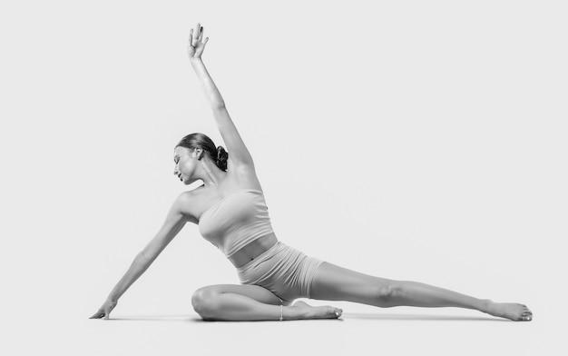요가 연습을 하 고 스포티 한 젊은 여자. 흰색 배경에 고립. 건강한 생활 방식과 신체와 정신 발달 사이의 자연스러운 균형의 개념. 필라테스, 스트레칭.