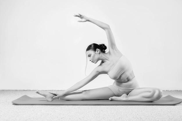 ヨガの練習をしているスポーティな若い女性。白い背景で隔離。健康的なライフスタイルと身体と精神の発達の間の自然なバランスの概念。ピラティス、ストレッチ。