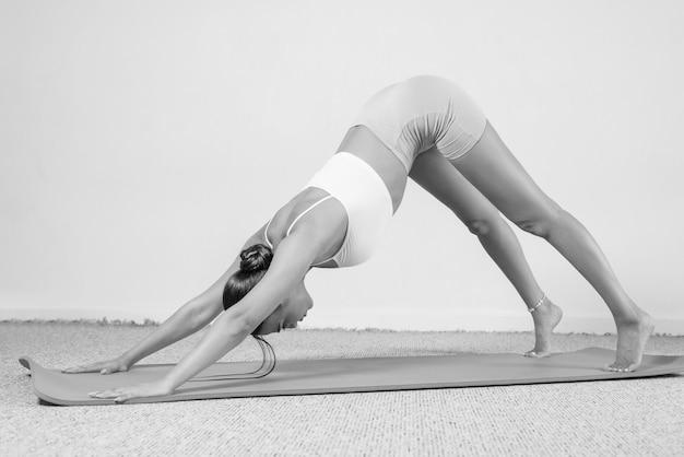 Спортивная молодая женщина занимается йогой. отдельный на белом фоне. концепция здорового образа жизни и естественного баланса между телом и умственным развитием. пилатес, растяжка.