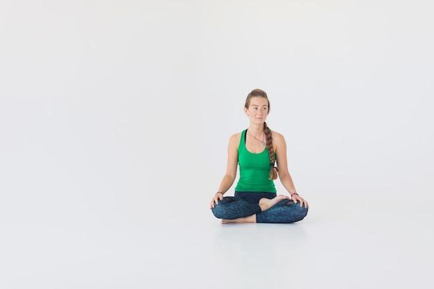 건강한 삶과 신체와 정신 발달 사이의 자연 균형의 개념-흰색 배경에 고립 된 요가 연습을 하 고 스포티 한 젊은 여자