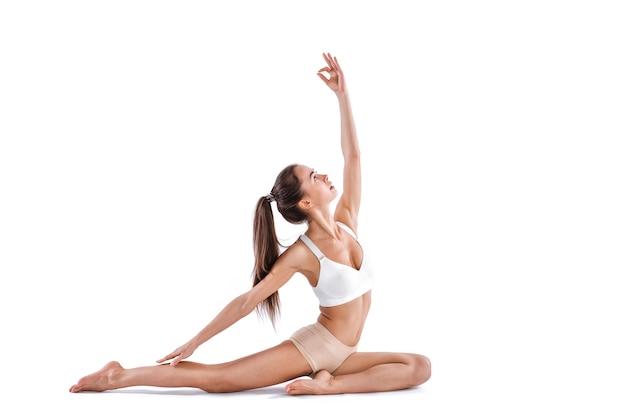 흰색 배경에 고립 된 요가 연습을 하 고 스포티 한 젊은 여자. 건강한 삶의 개념. 전체 길이.