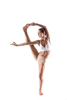 Спортивная молодая женщина делает практику йоги изолированной на белой предпосылке. упражнение control balance, студия во всю длину.