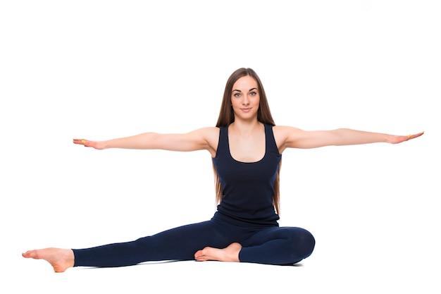 흰색 배경에 고립 된 요가 연습을 하 고 스포티 한 젊은 여자