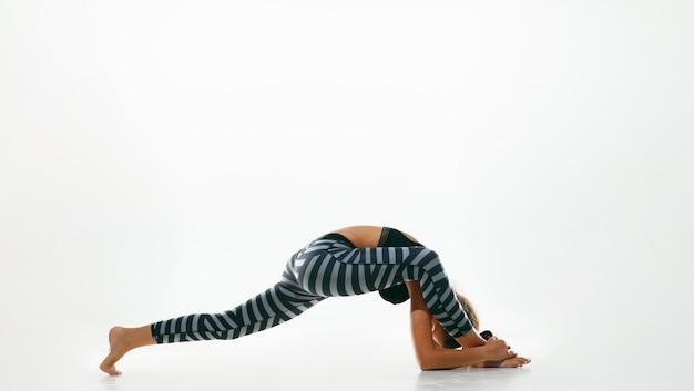 흰색 공간에 고립 된 요가 연습을 하 고 스포티 한 젊은 여자. 유연한 여성 모델 연습 적합
