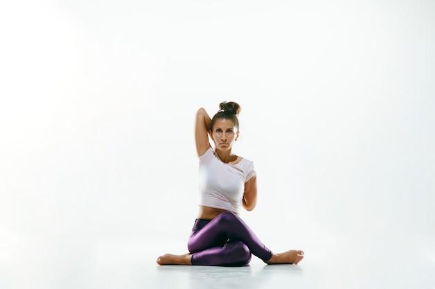 Спортивная молодая женщина делает практику йоги изолированной на белой предпосылке студии. подходит гибкая женская модель, практикующая. концепция здорового образа жизни и естественного баланса между телом и умственным развитием.