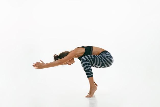 흰색 스튜디오 배경에 고립 된 요가 연습을 하 고 스포티 한 젊은 여자. 유연한 여성 모델 연습에 적합합니다. 건강한 생활 습관과 신체와 정신 발달 사이의 자연스러운 균형의 개념.