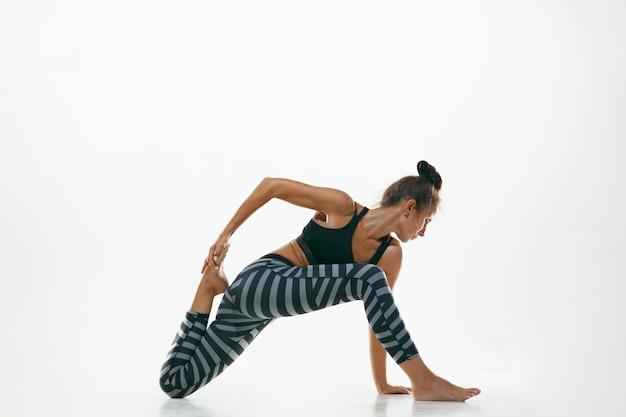 Спортивная молодая женщина делает практику йоги изолированной на белой стене. подходит гибкая женская модель, практикующая. концепция здорового образа жизни и естественного баланса между телом и умственным развитием.