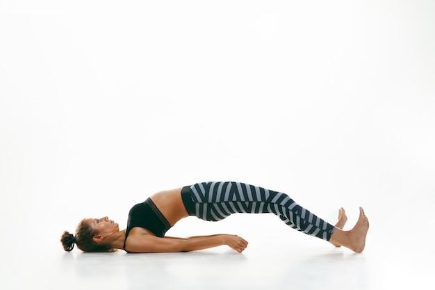 白い壁に隔離されたヨガの練習をしているスポーティな若い女性。練習中の柔軟な女性モデルにフィットします。健康的なライフスタイルと身体と精神の発達の間の自然なバランスの概念。