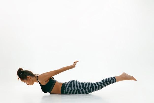 흰 벽에 고립 된 요가 연습을 하 고 스포티 한 젊은 여자. 유연한 여성 모델 연습에 적합합니다. 건강한 생활 습관과 신체와 정신 발달 사이의 자연스러운 균형의 개념.