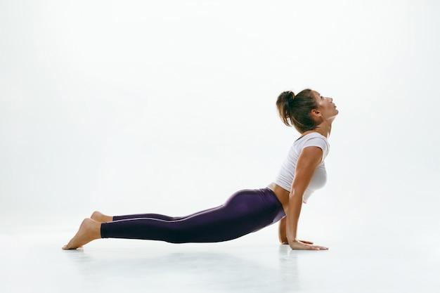 Giovane donna sportiva che fa pratica di yoga isolata su spazio bianco. fit modello femminile flessibile che pratica