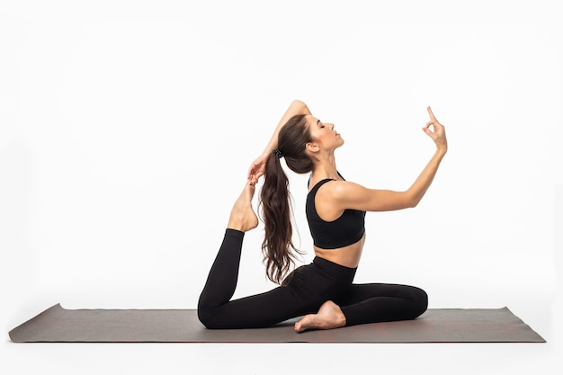 Sporty young woman doing yoga practice isolated on white surface - concept of healthy life and natural balance between body and mental development