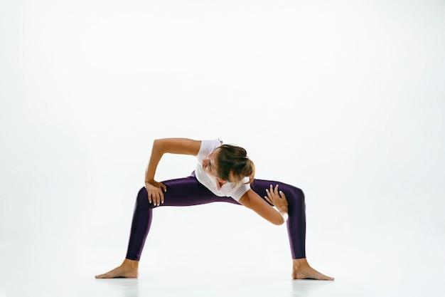 Giovane donna sportiva che fa pratica di yoga isolata sulla parete bianca. fit modello femminile flessibile che pratica. concetto di stile di vita sano e equilibrio naturale tra corpo e sviluppo mentale.