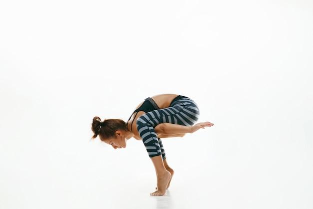 Giovane donna sportiva che fa pratica di yoga isolata su bianco
