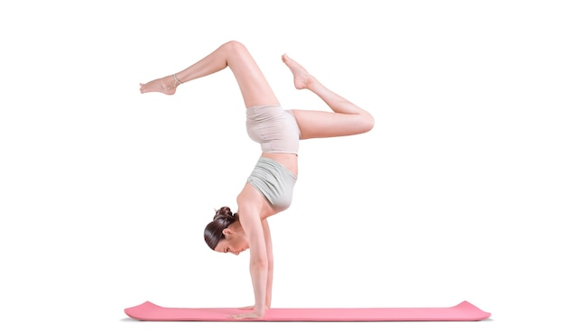 ヨガの練習をしているスポーティな若い女性。彼女は赤いマットの上に腕を組んで立っています。ミクストメディア
