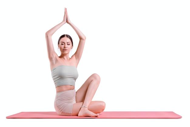 ヨガの練習をしているスポーティな若い女性。健康的なライフスタイルと心と体の自然なバランスのコンセプト。ピラティス、ストレッチ。ミクストメディア