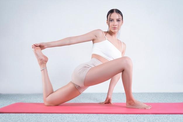 Спортивная молодая женщина занимается йогой. концепция здорового образа жизни и естественного баланса между телом и разумом. пилатес, растяжка. смешанная техника