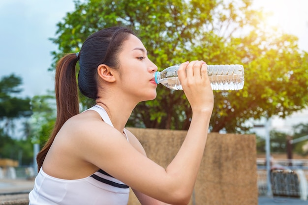 Sporty young woman drinking water after jogging.