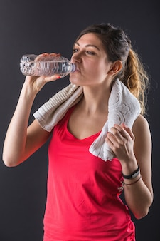 Sporty young woman drinking water on black