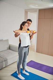 彼女の男の助けを借りて運動するスポーティな若い女性