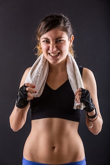 Sporty young woman grinding teeth on black
