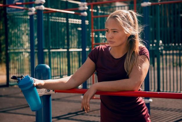 スポーツグラウンドでのトレーニング後にウォーターシェーカーを保持しているスポーティな若い女性