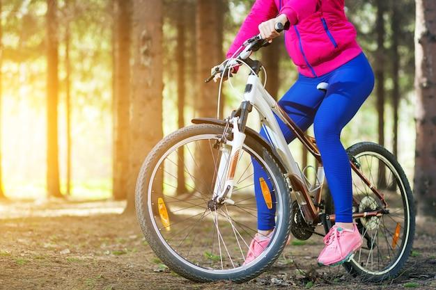 밝은 분홍색 재킷과 청바지에 스포티 한 젊은 여성이 숲을 통해 자전거를 타고