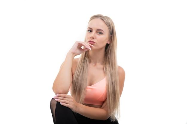 핑크 탑, 레깅스와 운동화 포즈에 스포티 한 젊은 여자
