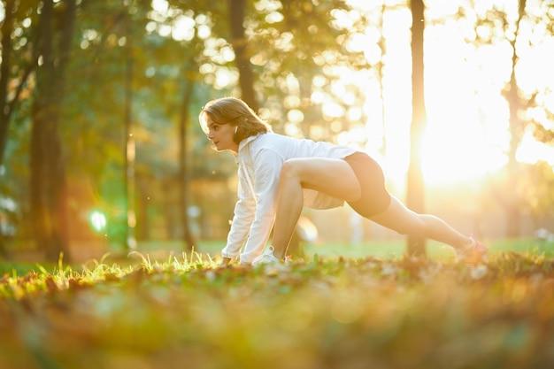 흰색 재킷과 검은색 반바지를 입은 스포티한 젊은 여성이 몸을 스트레칭하기 위한 운동을 합니다. 화창한 날 야외에서 갈색 머리 훈련을 하는 행복한 여성.
