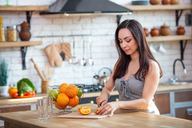 스포티 한 젊은 여자는 부엌에서 과일 주스에 대 한 신선한 오렌지를 절단입니다. 수평 실내 촬영.