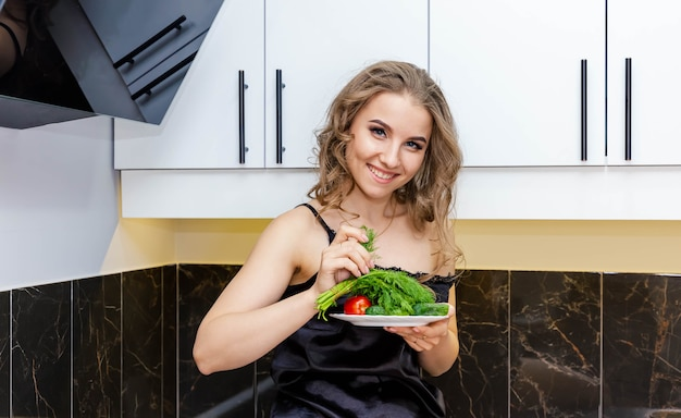 Sporty young woman is preparing healthy food on the kitchen