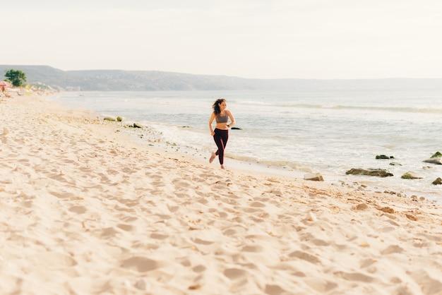 スポーティな若い女性が朝、ビーチを走っています。