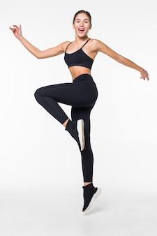 스포티 한 젊은 여성이 흰 벽에 고립 된 점프