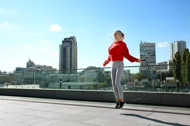 Спортивная молодая женщина, прыжки через скакалку на открытом воздухе