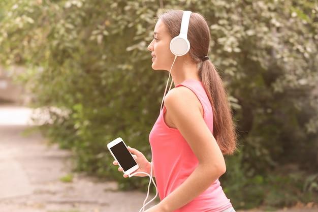 야외에서 음악을 듣고 스포티 한 젊은 여자