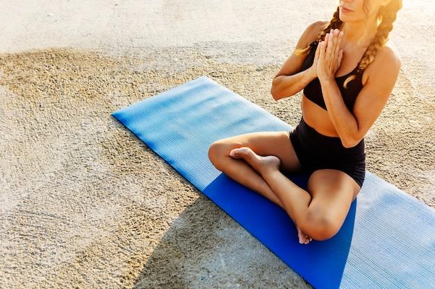 ビーチで蓮華座で瞑想するスポーティな若い女性-朝の屋外でヨガを練習する健康な若い女の子-ウェルネスとヘルスケアのライフスタイルの概念
