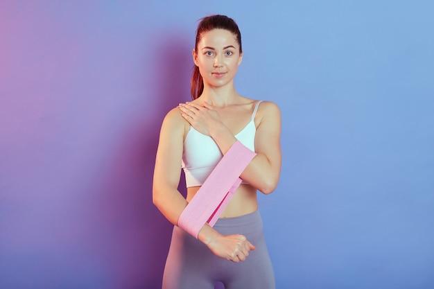 Спортивная модель молодой женщины в белой футболке без рукавов и леггинсах, делает спортивные упражнения на бицепс и трицепс с резиновыми лентами спортивного фитнеса, изолированными на цветном фоне.