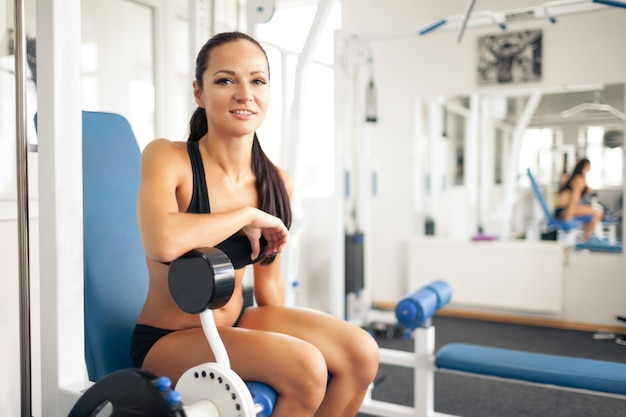 Sporty young woman posing in gym.