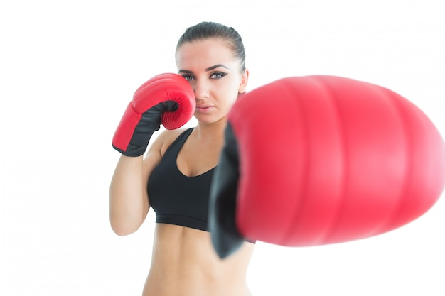 Sporty young woman posing wearing boxing gloves