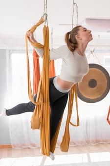 Спортивная молодая женщина занимается летной йогой в солнечном тренажерном зале для йоги с гамаками для хорошего самочувствия и здоровья