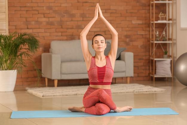 自宅でヨガを練習するスポーティな若い女性