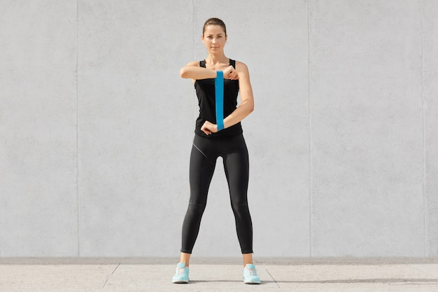Sporty young woman runner with elastic band, does exercises for hands, dressed in spotsclothes, sneakers, has dark hair, wants to have muscular body, models on grey concrete wall indoor