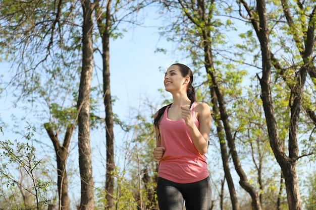 公園で走っているスポーティな若い女性