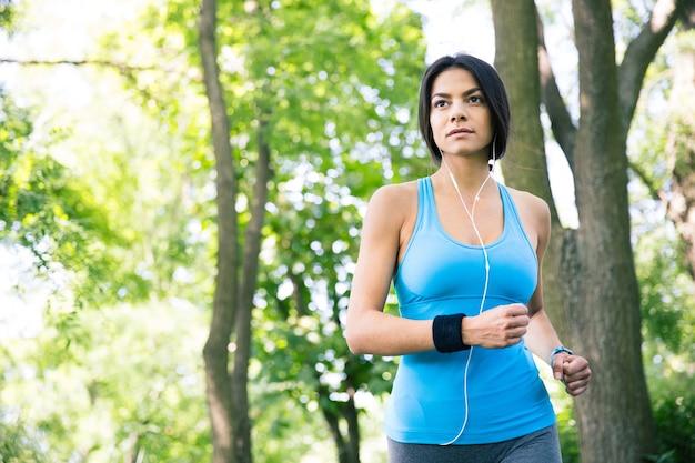 屋外で走っているスポーティな若い女性