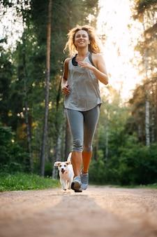 Спортивная молодая женщина бежит утром в парке с собакой джек рассел нагрузкой на сердце бегом