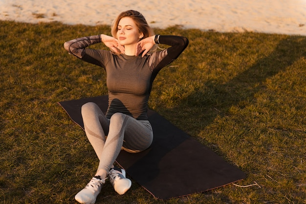 Sporty young woman sitting on yoga mat near playground with closed eyes. the girl enjoys the sunset after an active workout.
