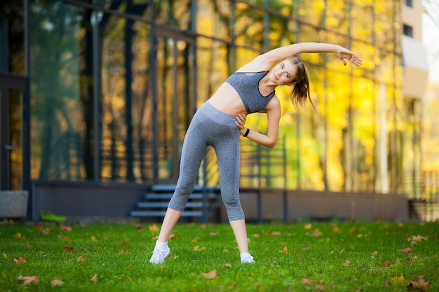 Sporty young woman in sportswear doing stretching after fitness exercises